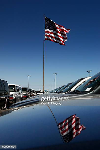 An American flag flies over cars in the lot of a car dealership
