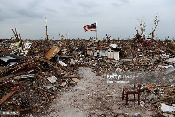 An American flag flies over the rubble of a destroyed neighborhood on May 24 2013 in Moore Oklahoma The tornado of EF5 strength and two miles wide...