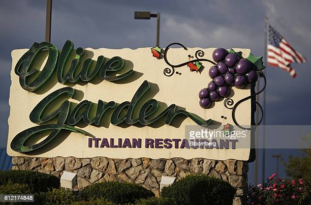 An American flag flies past a Darden Restaurants Inc Olive Garden location in Clarksville Indiana US on Wednesday Sept 28 2016 Darden Restaurants Inc...