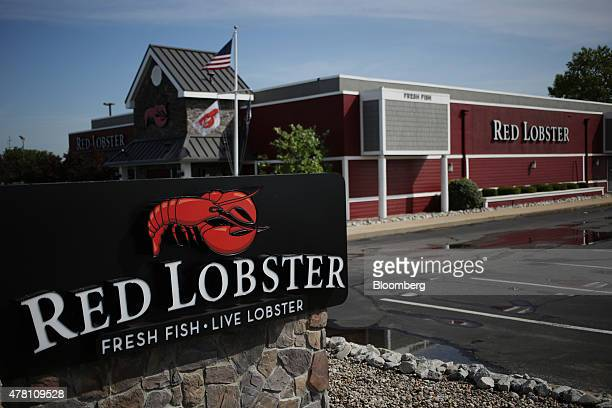 An American flag flies past Red Lobster signage displayed outside of a restaurant location in Clarksville, Indiana, U.S., on Monday, June 22, 2015....