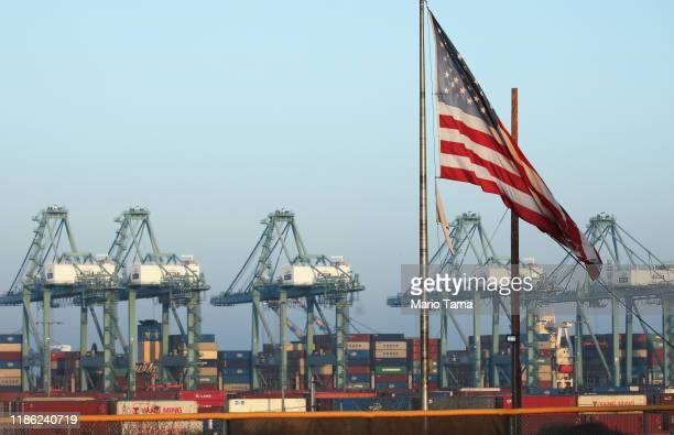 An American flag flies with shipping containers stacked at the Port of Los Angeles in the background which is the nation's busiest container port on...