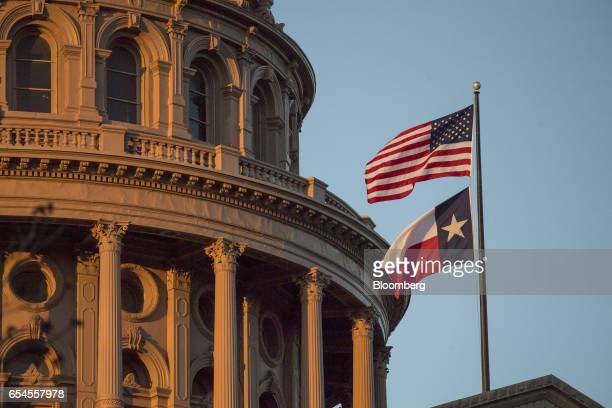 An American flag flies with the Texas state flag outside the Texas State Capitol building in Austin Texas US on Tuesday March 14 2017 Austin has...