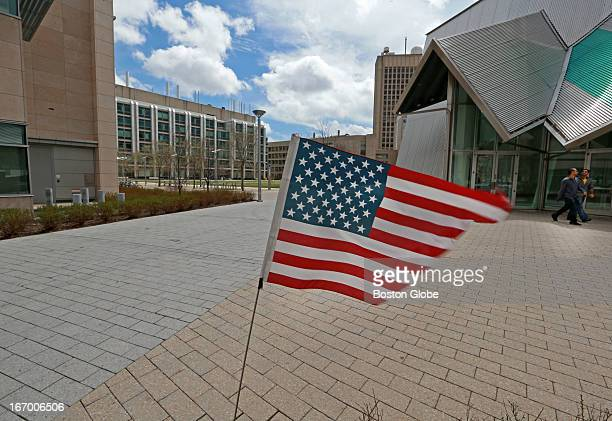 An American flag flutters in the wind at the scene of the murder of MIT police officer Sean Collier. Part of the MIT Koch Institute is at far left,...