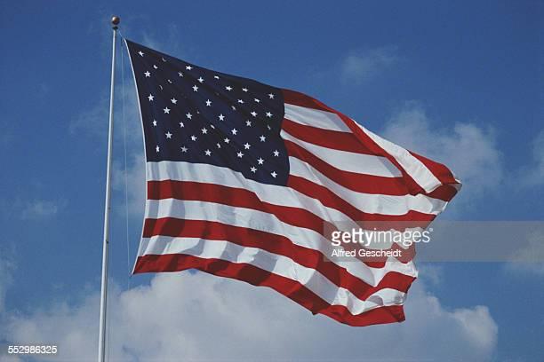 An American flag flying against a blue sky circa 1990