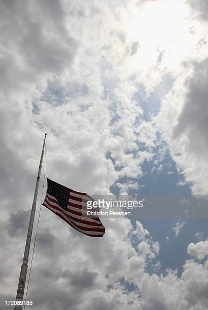 An American flag flys at half mast to honor the 19 Granite Mountain Interagency Hotshot Crew firefighters who died Sunday while battling a fastmoving...
