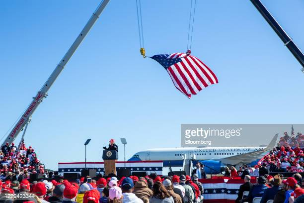 An American flag hangs above attendees as U.S. President Donald Trump speaks during a campaign rally in Fayetteville, North Carolina, U.S., on...