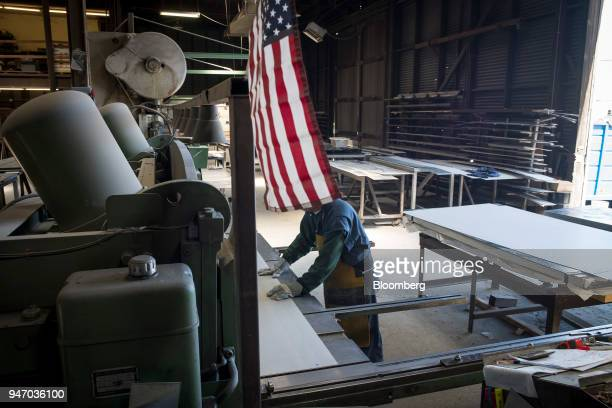 An American flag hangs as a worker operates a metal cutter at the Metal Manufacturing Co facility in Sacramento California US on Thursday April 12...
