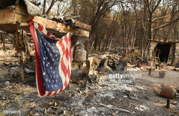 An American flag hangs at a burned out mobile home park in Paradise California on November 18 2018 The family lost a home in the same spot to a fire...