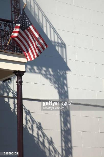 an american flag hangs from a balcony - timothy hearsum stockfoto's en -beelden