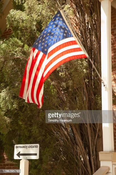 an american flag hangs from a porch post in a small town - timothy hearsum photos et images de collection