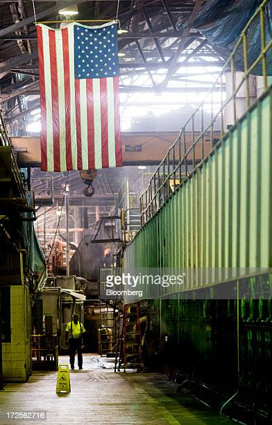 An American flag hangs from the ceiling as a worker walks near the paper mill at Newark Recycled Paperboard Solutions in Baltimore Ohio US on Tuesday...
