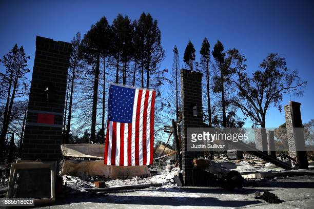An American flag hangs in front of a home in the Coffey Park neighborhood that was destroyed by the Tubbs Fire on October 23 2017 in Santa Rosa...