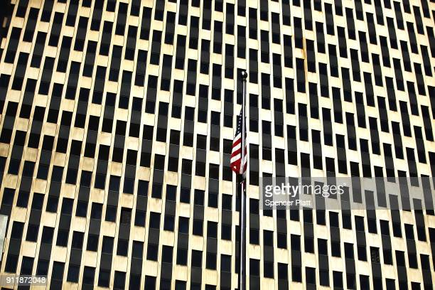 An American Flag hangs in front of the federal building as dozens of immigration activists clergy members and others participate in a demonstration...