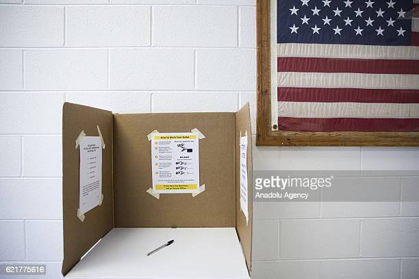An American Flag hangs on a wall next to a polling booth in Loudon County High School during the 2016 Presidential Elections in Leesburg Va USA on...