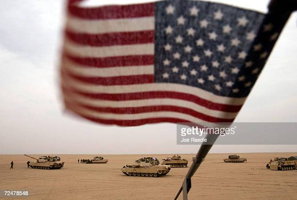 An American flag hangs on an antennae of a tank as US Army M1A1 Abrams tanks and Bradley fighting vehicles prepare to take part in an exercise...