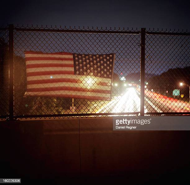 CONTENT] An American flag hangs over a highway underpass Cars are streaming by as the american flag blows in the wind It is nighttime in the summer