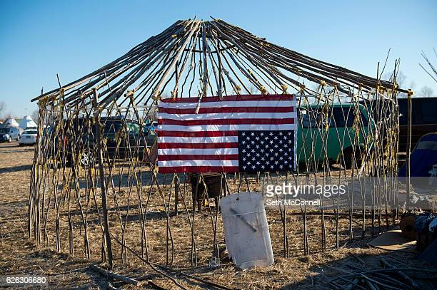 An American Flag hangs upside down on the side of a yurt still under construction at Oceti Sakowin Camp on the Standing Rock Sioux Reservation in...