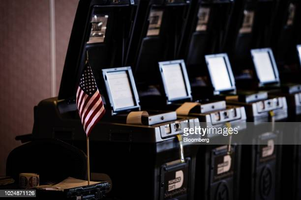 An American flag is displayed next voting machines at a polling station in Doral Florida US on Tuesday Aug 28 2018 The Senate contest in Florida is...