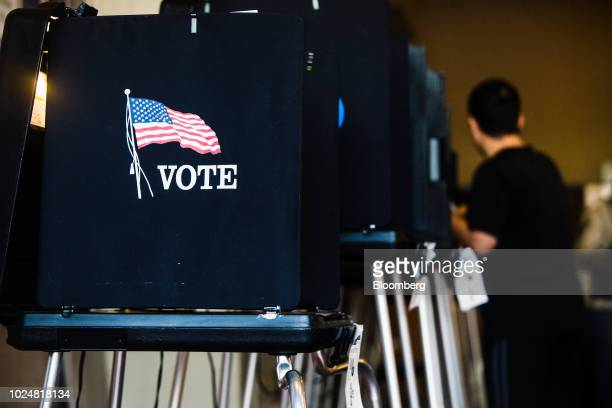 An American flag is displayed on a privacy voting booth at a polling location in Miami Beach Florida US on Tuesday Aug 28 2018 The Senate contest in...