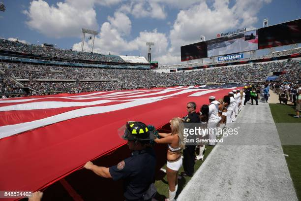 An American flag is displayed on the field prior to the start of the game between the Tennessee Titans and the Jacksonville Jaguars at EverBank Field...