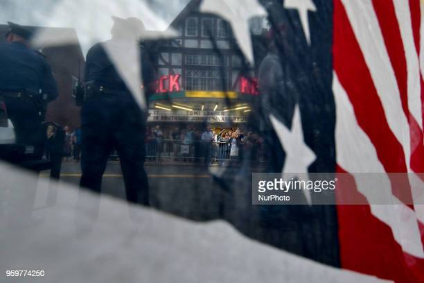 An American Flag is draped over police tape as protestors and fans face off on opposing sides of the street ahead of a tour stop by Tomi Lahren...