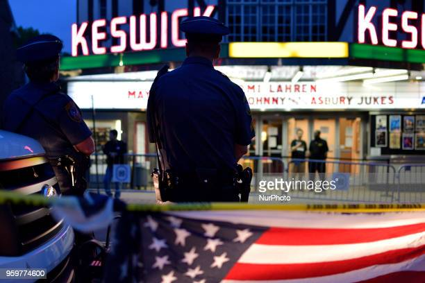 An American Flag is light by headlights of a Police cruiser as protestors and fans face off on opposing sides of the street ahead of a tour stop by...