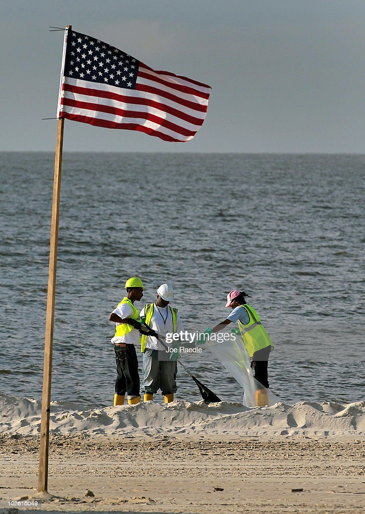 An American flag is pitched in the sand as workers clear off some of the oil residue on the beach from the Deepwater Horizon oil spill in the Gulf of Mexico on July 4, 2010 in Pass Christian, Mississippi. The oil spill may have a huge negative economic impact on gulf coast businesses during what should be a busy 4th of July. Millions of gallons of oil have spilled into the Gulf since the April 20 explosion on the drilling platform.