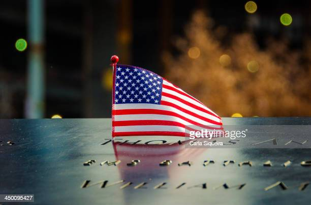 CONTENT] An American flag is placed next to the names inscribed on the edge of one of the World Trade Center Memorial