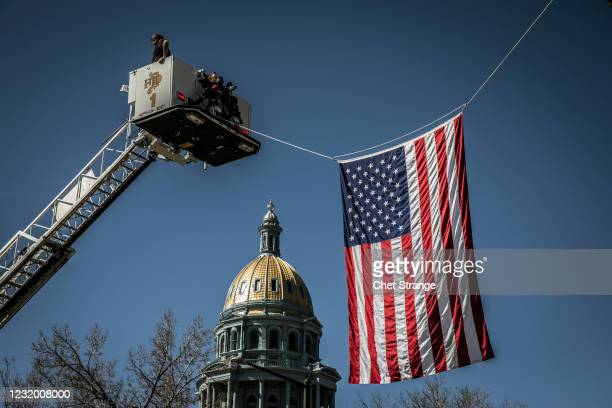 An American Flag is placed over Colfax Avenue during a Funeral Mass for slain Boulder Police officer Eric Talley at The Cathedral Basilica of the...