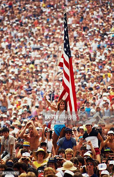 An American flag is raised in the crowd during the US Live Aid concert held to raise money for famine victims in Ethiopia at the John F Kennedy...