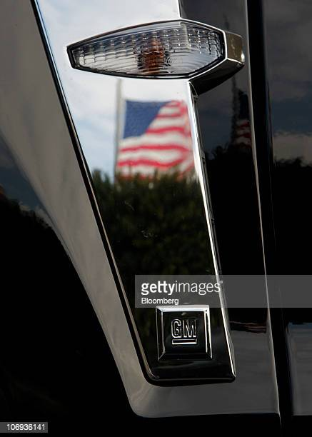 An American flag is reflected in the trim of a General Motors Co. Cadillac SRX at Don Massey Cadillac in Plymouth, Michigan, U.S., on Wednesday, Nov....