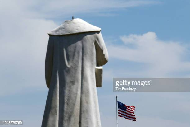 An American flag is seen in front of a statue depicting Christopher Columbus which had its head removed at Christopher Columbus Waterfront Park on...