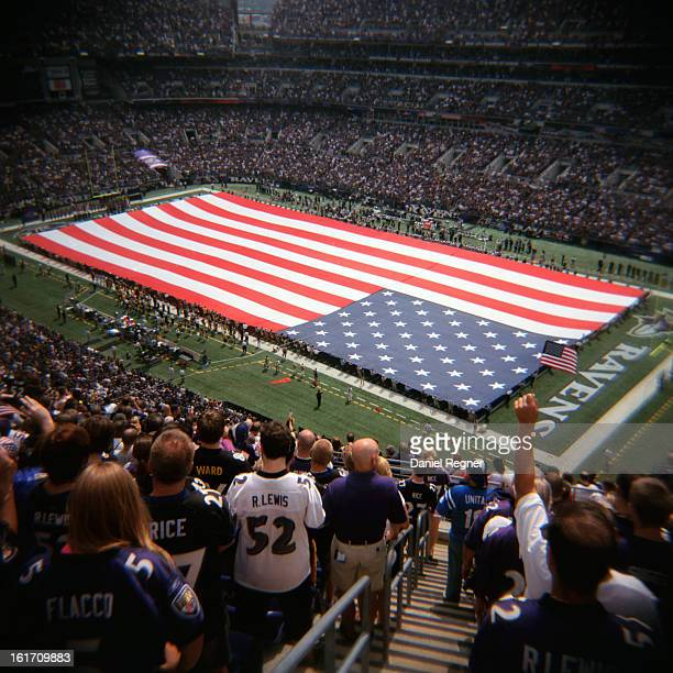 An American flag is spread across an NFL football field, showing the american spirit. The Red, White, and Blue can be seen bright and happy with...