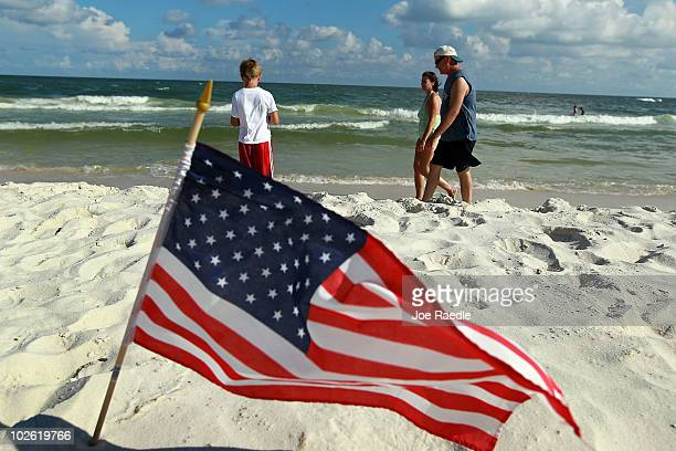 An American flag is stuck in the sand as people walk along a beach which was not as busy as last year as people stayed away due to the threat of...
