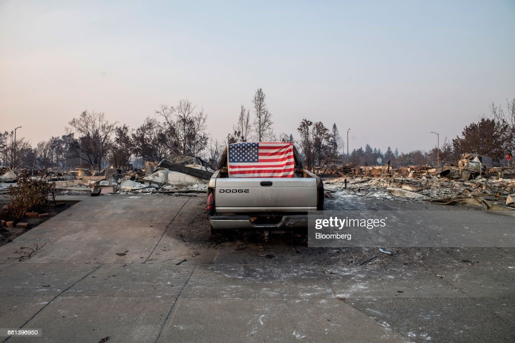 An American flag is taped on the back of a pick up truck standing in front of residences burned by wildfires in Santa Rosa, California, U.S., on Friday, Oct. 13, 2017. Wildfires that tore through northern California's iconic wine-growing regions have prompted evacuations of more than 20,000 people, killed 11 and damaged some of the most valuable vineyards and wineries in the U.S. About 1,500 commercial, residential and industrial structures were burned, and damage assessment teams have started accounting for the destruction. Photographer: David Paul Morris/Bloomberg via Getty Images