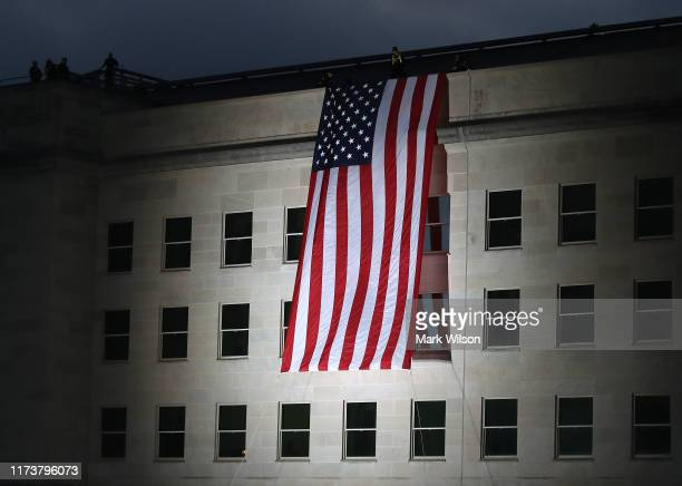 An American flag is unfurled on the side of the Pentagon to commemorate the anniversary of the 9/11 terror attacks September 11 2019 in Arlington...
