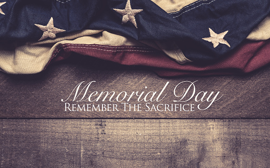 An American flag or bunting on a wooden background with memorial day greeting 956491574