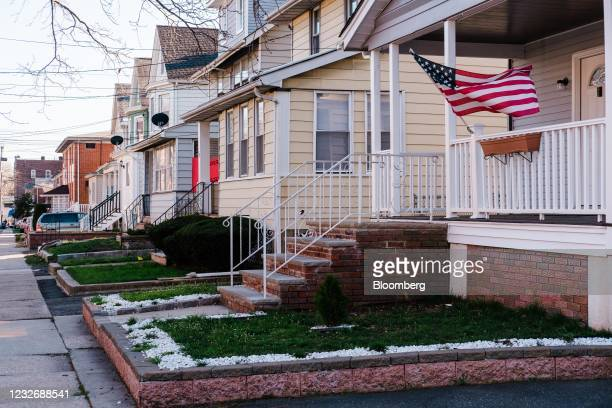 An American flag outside a home in Irvington, New Jersey, U.S., on Tuesday, March 30, 2021. The U.S. Economy is on a multi-speed track as minorities...