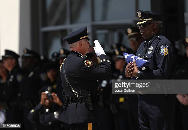 An American flag that draped the casket of slain Dallas Area Rapid Transit police officer Brent Thompson is passed off before given to the family...