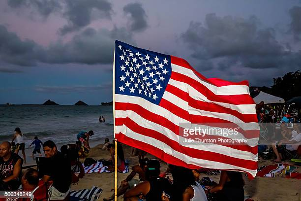 An American Flag waves in the sand as crowds and families gather to watch the spectacular Fourth of July fireworks show at the world famous travel...