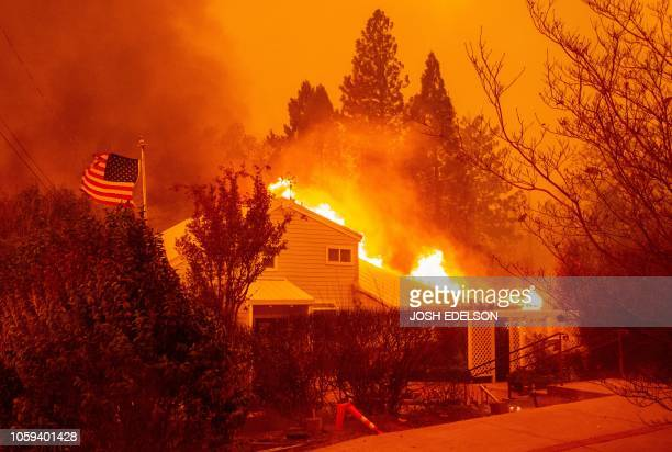 An American flag waves in the wind as a home burns during the Camp fire in Paradise, California on November 8, 2018. - More than 18,000 acres have...