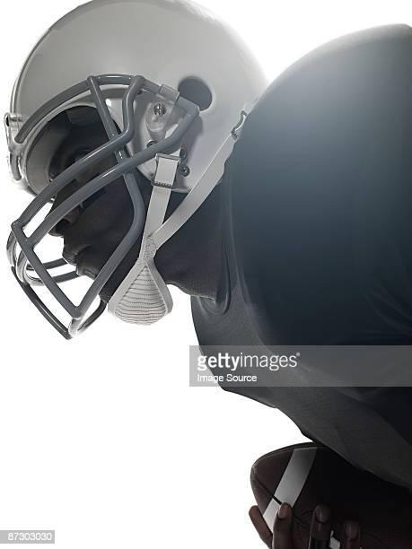 An american football player holding a football