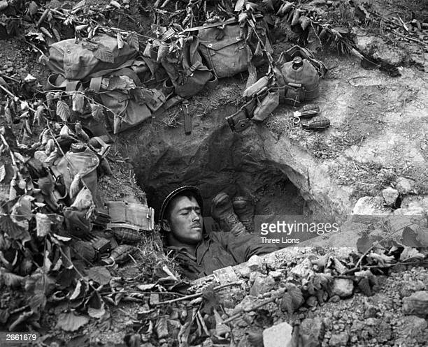 An American GI asleep in a trench in Normandy