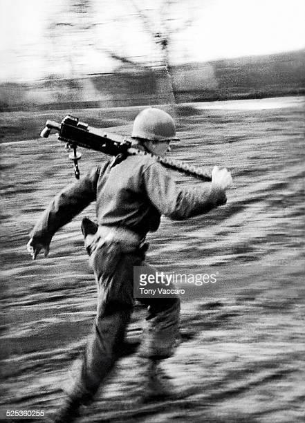 An American GI runs with a machine gun during the Battle of the Bulge Ardennes Belgium World War II January 1945