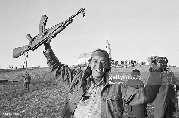 An American Indian Movement soldier waves an AK47 automatic weapon in a victory salute after learning of a cease fire agreement between AIM forces...