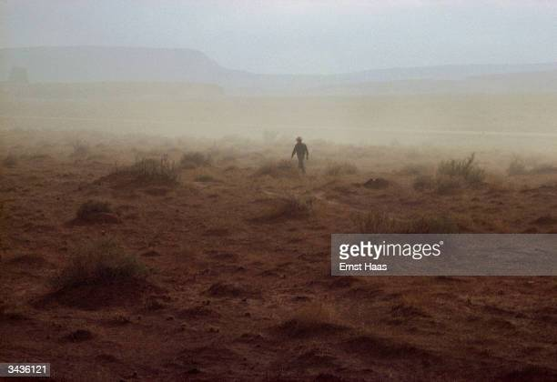 An American Indian walks through the yellow landscape of a Nevada duststorm