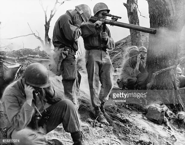 An American infantryman fires a 75mm rocket launcher during the Korean War as his fellow soldiers cover their ears