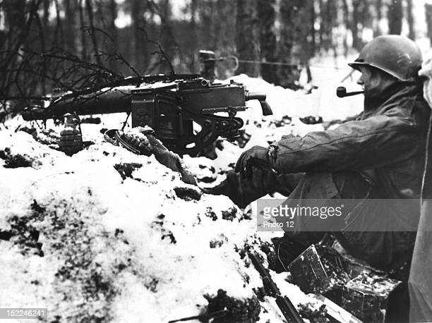 An American infantryman take time out for a pipe smoke during a lull in the fighting during the Battle of the Bulge
