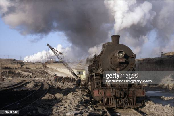 An American inspired JF Class Mikado 282 heads a track slewing engineer's train in the vast opencast coalmine at Manzhouli on China's Russian border...