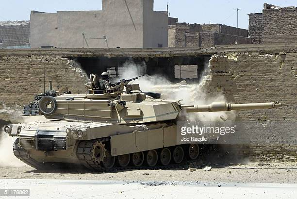 An American M1 Abrams tank from the 1st Cavalry Division 2nd Battalion 7th Cavalry breaches a wall to let infantry look inside after they came under...